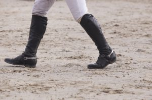 Rider walking a course at horse jumping competition. Boots details